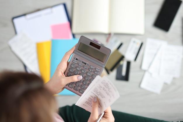 Vrouw houdt rekenmachine en betaalde cheque kostenbeheersing concept