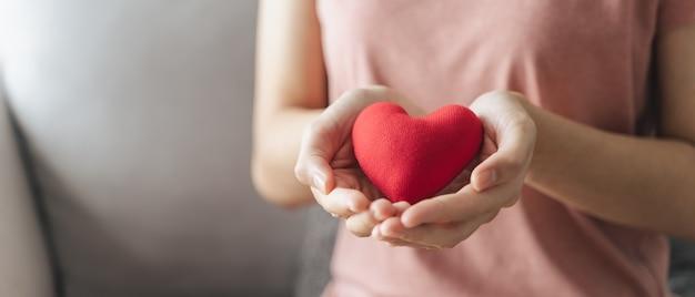 Vrouw houdt rood hart liefde ziektekostenverzekering donatie gelukkige liefdadigheid vrijwilliger geestelijke gezondheid dag