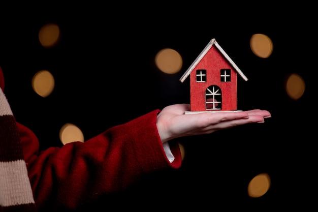 Vrouw houdt rood speelgoed huis in een hand