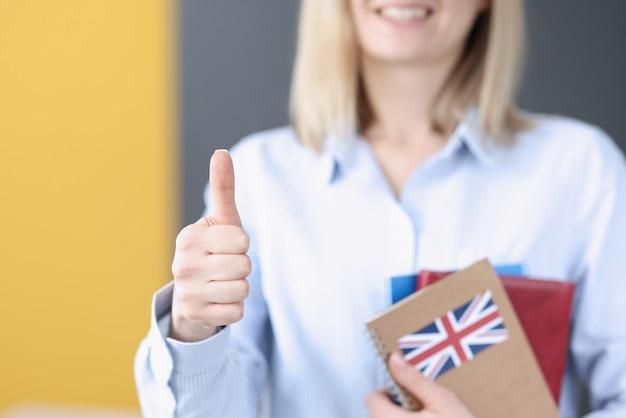 Vrouw houdt schoolboeken met britse vlag en duimen opdagen. hoger onderwijs in engeland voor