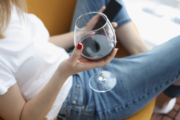 Vrouw houdt smartphone en glas wijn in haar handen