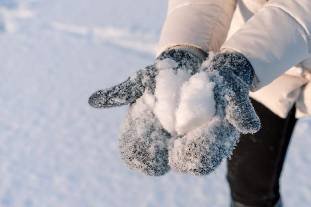 Vrouw houdt sneeuw in blauwe wanten