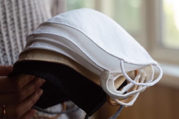 Vrouw houdt stapel zelfgemaakte beschermende herbruikbare antivirale maskers vast