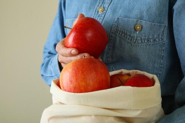 Vrouw houdt tas met rijpe rode appels vast