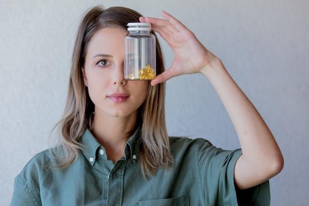 Vrouw houdt transparante pot met pillen op ooghoogte. zijaanzicht