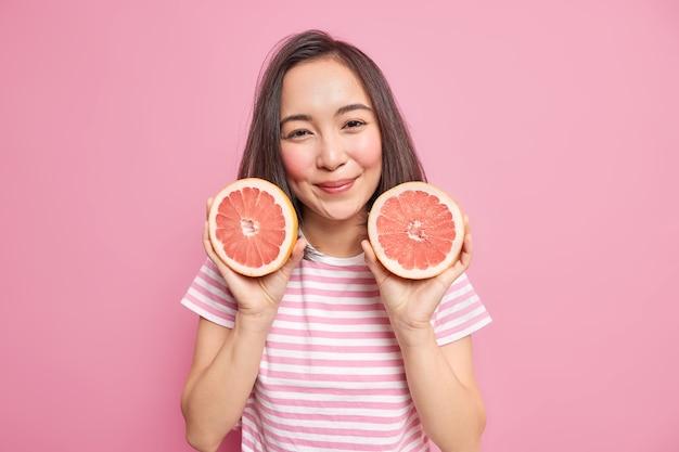 Vrouw houdt twee helften grapefruit vast eet citrusvruchten om vitamines te krijgen om sap te maken houdt zich aan een gezond dieet draagt gestreept t-shirt
