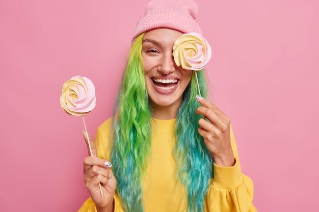 Vrouw houdt twee ronde snoepjes op stokken tegen oog met heerlijke karamel lolly heeft kleurrijk haar draagt gele trui en hoed geïsoleerd op roze