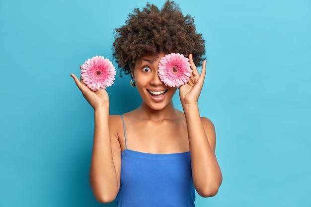 Vrouw houdt van geurige bloemen plukt twee roze gerbera's bedekt ogen heeft plezier geniet van aangenaam aroma