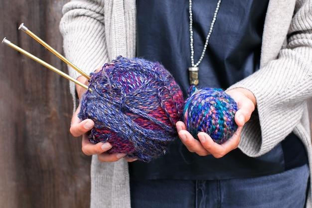 Vrouw houdt veelkleurige heldere ballen van wollen garen om te breien. breigaren, breinaalden, strengen. mooie kleuren om te breien. handgemaakt creatief breiconcept.