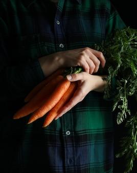 Vrouw houdt verse wortel tegen donkere ondergrond