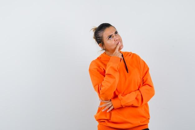 Vrouw houdt vinger op de lippen in oranje hoodie en kijkt peinzend