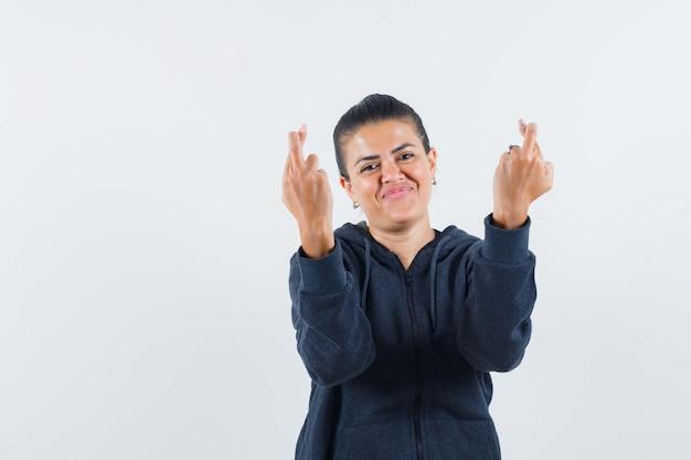 Vrouw houdt vingers gekruist in hoodie en ziet er vrolijk uit. vooraanzicht.