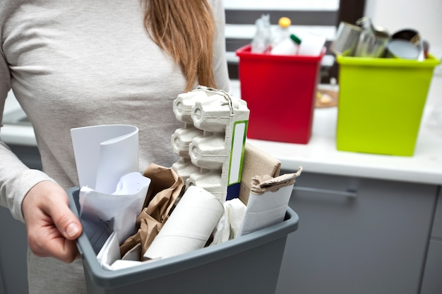 Vrouw houdt vol plastic doos met diverse papierafval