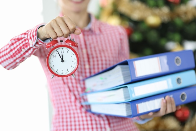 Vrouw houdt wekker voor twaalf uur en stapel documenten tegen de achtergrond van