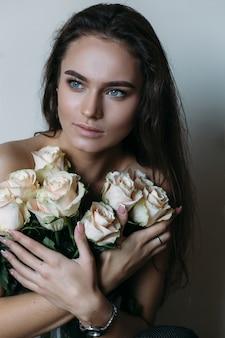 Vrouw houdt witte rozen voor haar borst
