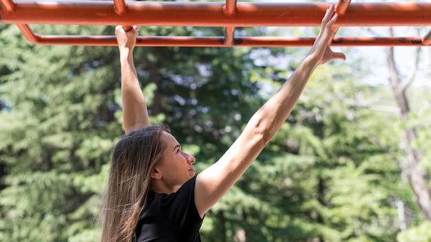 Vrouw houdt zichzelf voor op een metalen staaf