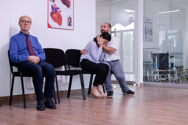 Vrouw huilend in de armen van haar echtgenoot zittend in de wachtruimte van het ziekenhuis