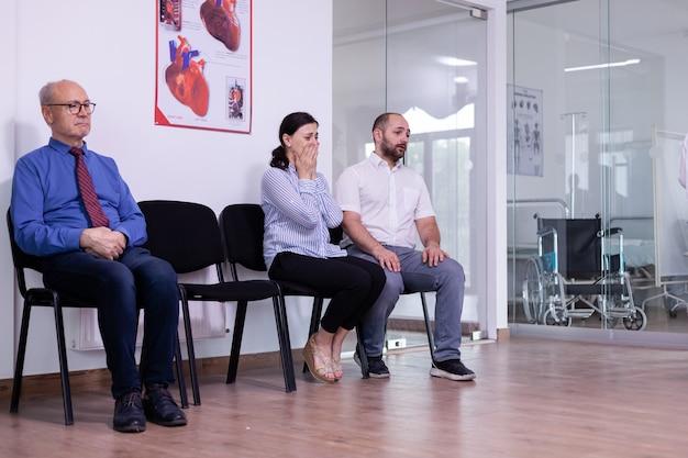 Vrouw huilt na slecht nieuws van dokter in wachtkamer ziekenhuis