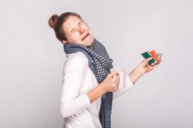 Vrouw huilt omdat ze ziek was. kopje met thee, veel pillen en antibiotica vasthouden. studio-opname, geïsoleerd op een grijze achtergrond