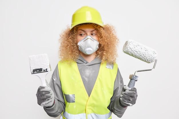 Vrouw huisschilder houdt schilderborstel roller draagt veiligheidshelm gasmasker en uniform verven huisbenodigdheden reparatieservice