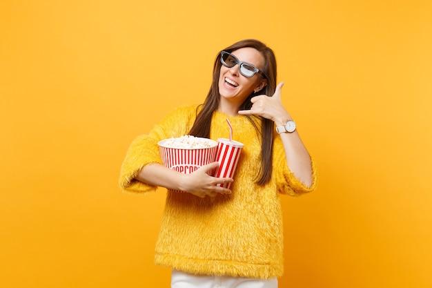 Vrouw in 3d imax-bril kijken naar filmfilm in bioscoop met popcornkopje frisdrank doet telefoongebaar zoals zegt: bel me terug met vingers zoals praten aan de telefoon geïsoleerd op gele achtergrond.