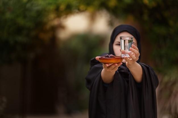 Vrouw in abaya met een dadelfruit en een glas water in van de herviering van ramadan
