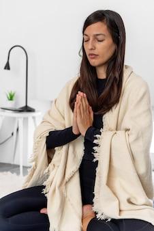 Vrouw in activewear en sjaal mediteren in lotus houding met namaste handen tijdens yogasessie