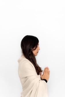 Vrouw in activewear en sjaal mediteren met namaste handen op witte achtergrond tijdens yogasessie
