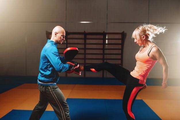 Vrouw in actoin op zelfverdedigingstraining met persoonlijke instructeur, vechttraining in de sportschool, krijgskunst