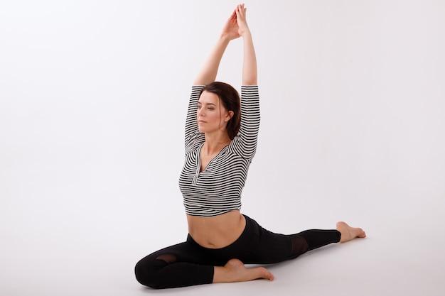 Vrouw in asana op een witte geïsoleerde achtergrond. internationale yogadag
