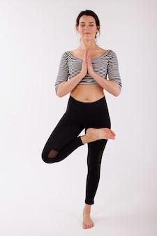 Vrouw in asana op een witte geïsoleerde achtergrond. yoga en meditatie doen. internationale yogadag