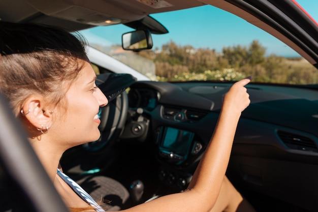 Vrouw in auto die en vooruit hand glimlacht toont
