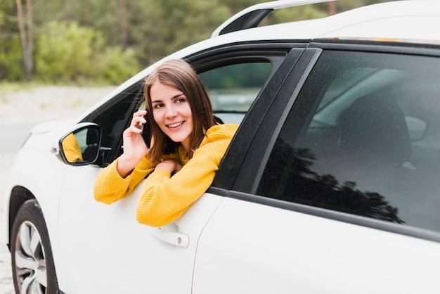 Vrouw in auto die op de telefoon spreekt