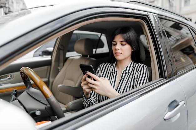 Vrouw in auto maakt gebruik van telefoon