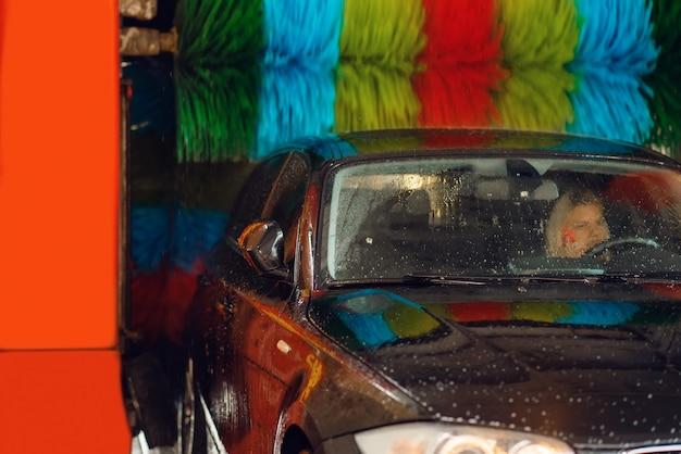 Vrouw in auto op automatische autowasstraat met kleurrijke borstel