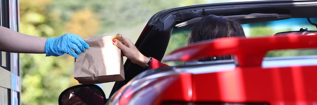 Vrouw in auto pakt zak met voedsel close-up