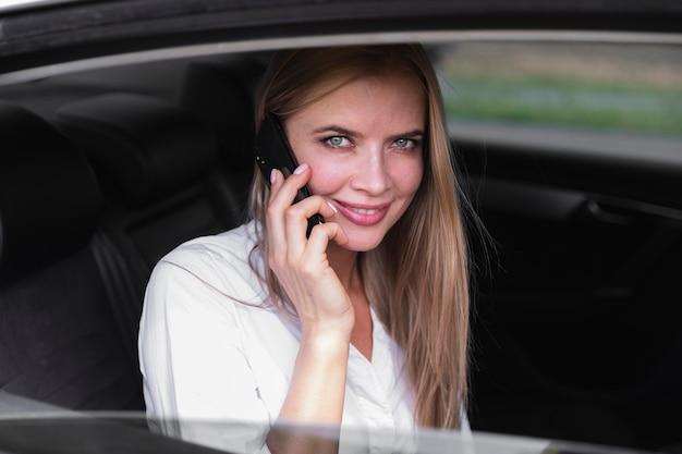 Vrouw in autoachterbank die op telefoon spreekt