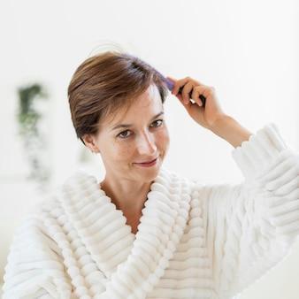 Vrouw in badjas haar haren borstelen en glimlachen