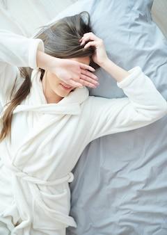 Vrouw in badjas in haar bed