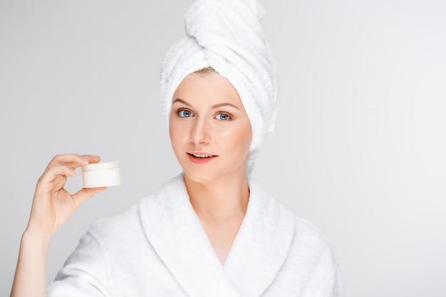 Vrouw in badjas met crème, huidverzorging product promo