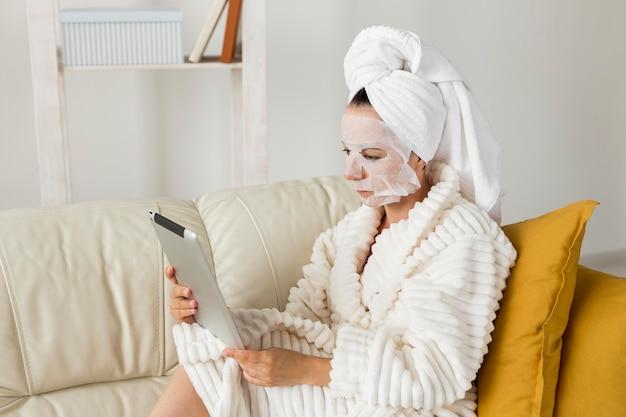Vrouw in badjas met gezichtsmasker met haar tablet