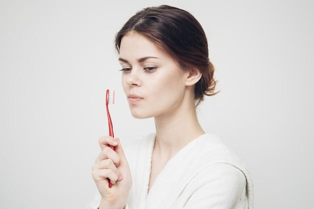 Vrouw in badjas tanden poetsen