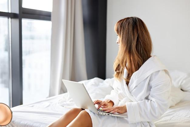 Vrouw in badjas zittend op een breed wit bed, typen op een laptop, werken in de ochtend thuis. zijaanzicht. levensstijl concept