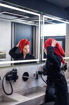 Vrouw in badkamer die haar droogt Premium Foto