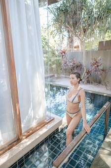 Vrouw in badkleding die het zwembad uitloopt.