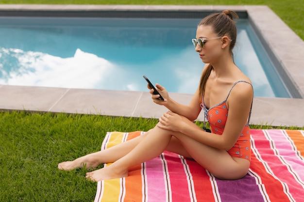 Vrouw in badmode met behulp van mobiele telefoon bij het zwembad in de achtertuin
