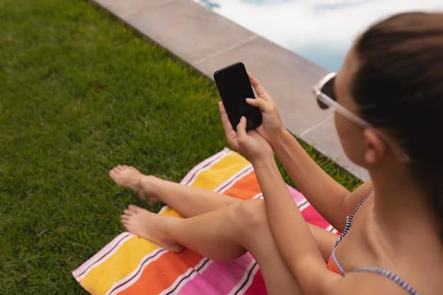 Vrouw in badmode met behulp van mobiele telefoon bij het zwembad