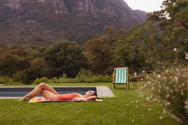 Vrouw in badmode ontspannen in de buurt van het zwembad in de achtertuin