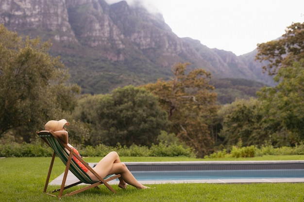 Vrouw in badmode ontspannen op een ligstoel in de buurt van het zwembad in de achtertuin