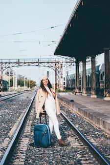 Vrouw in baret en beige jas wachten op trein op een treinstation.